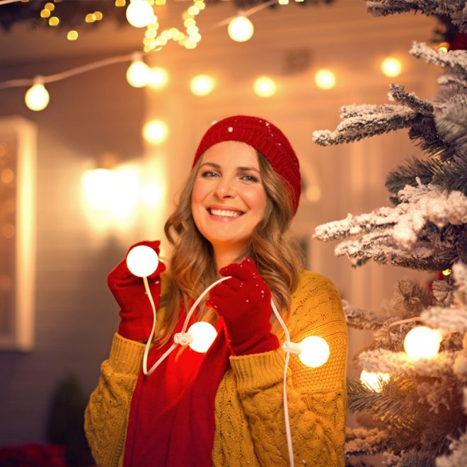 Woman in red toque and mitts decorating her home and yard