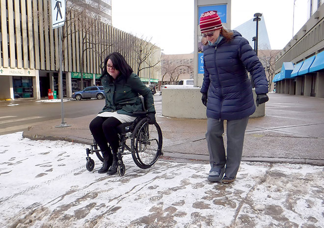 Two people crossing a snowy street, one on foot and the other in a wheelchair.
